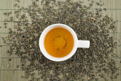 White cup of black tea. On scattered tea over bamboo mat Stock Photos