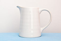 White cup on blue cloth Royalty Free Stock Images