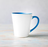 White cup with blue handle and inner surface Stock Image