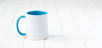 White cup with blue handle and inside Stock Image