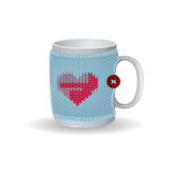 White cup with a blue knitted cover. On the cover design with red heartand a button. Vector winter illustration to Valentine`s Day. Isolate Stock Images