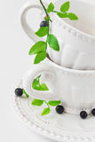 White cup and a branch with blueberries Royalty Free Stock Photos