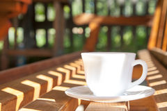 White cup  on a brown bench Stock Photos