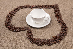 White cup of on burlap with coffee heart. Cup of on burlap with coffee beans heart Royalty Free Stock Photo
