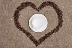 White cup of on burlap with coffee heart top. White cup of on burlap with coffee beans heart top view Royalty Free Stock Photo