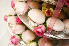 White cup cakes. Iced tea time cup cakes with pink roses on display Stock Image
