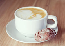 White cup of cappuccino with chocolate cookie; selective focus Stock Images