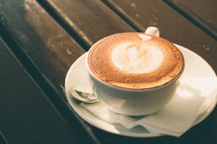 White cup of cappuccino with cinnamon on a wooden table in a caf Royalty Free Stock Images