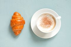 White cup of cappuccino with fresh croissant on the light blue table royalty free stock photo