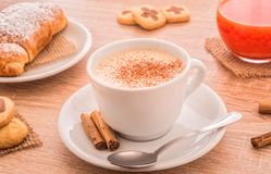 White cup of cappuccino , pastries and cookies. Still life composition with a cup cappuccino over a wooden table with assorted pastries and cookies and orange Stock Photography