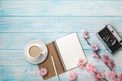 White cup cappuccino with sakura flowers, notebook and old photo camera on a blue wooden table royalty free stock photo