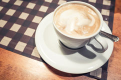 White cup of cappuccino stands on wooden table Stock Photography