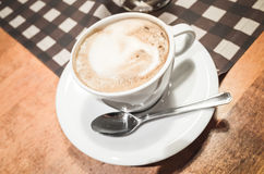 White cup of cappuccino stands on wooden table Stock Image