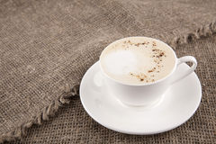 White cup of cappuchino on burlap. Cup of capuccino in white cup on black background Stock Photos