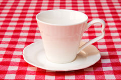 White cup on the checkered tablecloth Royalty Free Stock Image
