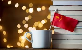 White cup with China flag near books. On fairy lights background royalty free stock image