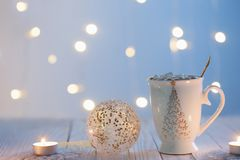 White cup with  chritmas ball on white wooden table stock photography