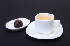 White cup of classic espresso coffee and pralines on black background. Royalty Free Stock Images