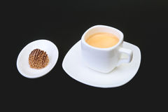 White cup of classic espresso coffee and pralines on black background. Stock Image