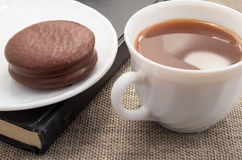 White cup with cocoa and chocolate biscuit on old book Stock Photo