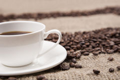 White cup of coffe on burlap. Cup of coffee  in white cup on burlap Royalty Free Stock Photo