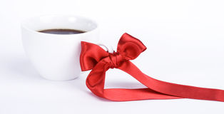 White cup of coffe with red bow. On white background Royalty Free Stock Photos