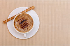 White cup coffe and waffle roll with cream on brown background Royalty Free Stock Image
