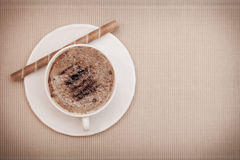White cup coffe and waffle roll with cream on brown background Stock Image