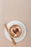 White cup coffe and waffle roll with cream on brown background Royalty Free Stock Photography