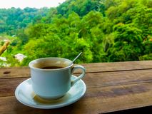 A white cup of coffe with wooden table royalty free stock images