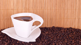 White cup of coffee. On coffee beams Royalty Free Stock Image