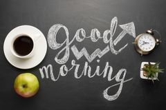 A white cup of coffee with an alarm clock and an apple and a good morning inscription. Concept of a cheerful and kind morning stock image