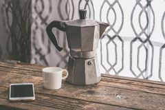 White cup of coffee and an aluminium coffe machine stock photos