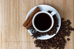 White cup of coffee with anise and cinnamon sticks.  Stock Photography