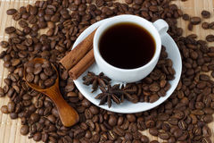 White cup of coffee with anise, cinnamon sticks and a spoon.  Stock Image