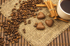 White cup of coffee on a background of wood and burlap, surrounded by coffee and cinnamon grains. Royalty Free Stock Image