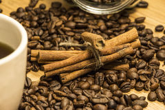 White cup of coffee on a background of wood and burlap, surrounded by coffee and cinnamon grains. Stock Photography