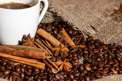 White cup of coffee on a background of wood and burlap, surrounded by coffee and cinnamon grains. Stock Images