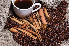 White cup of coffee on a background of wood and burlap, surrounded by coffee and cinnamon grains. Stock Photos