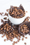 White cup with coffee beans Stock Images