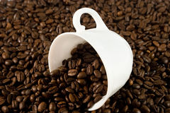 White cup with coffee beans. (with coffee beans as a background Royalty Free Stock Images