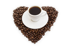 White cup of coffee on  beans as a heart Stock Image