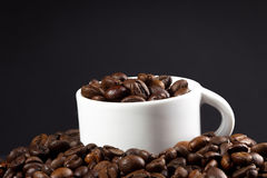 White cup and coffee beans. On dark background Royalty Free Stock Photography