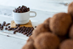 White cup with coffee beans. Stock Images