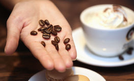White cup of coffee with beans. On the desk Royalty Free Stock Photo