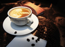 White cup of coffee with beans. On the desk Stock Image