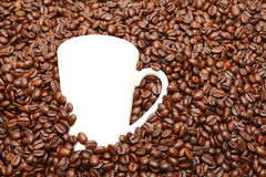 White cup in coffee beans Stock Photos