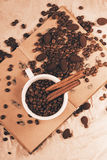 White cup of coffee beans on old book Stock Images