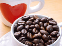 White cup of coffee beans with red heart on side of cup royalty free stock image