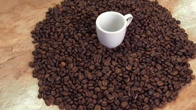 White cup of coffee beans. A small white cup on a coffee cup. In the kitchen on the table. stock footage